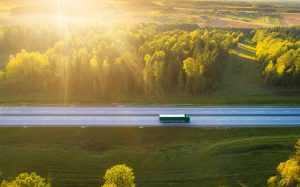 green-truck-morning-timedriving-on-highway-surrounded-by-forrest-smaller